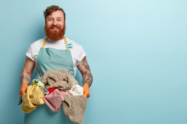 Glad satisfied red haired man happy finish domestic work, holds pile of fresh clean laundry, wears casual t shirt with apron and clothespins