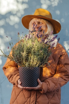 Радостная женщина старшего возраста в стильной верхней одежде и шляпе, улыбаясь в камеру и несущая лаванду в горшке