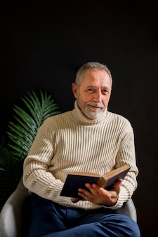 Glad senior man with book