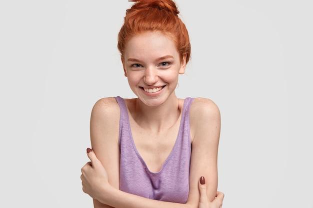 嬉しい恥ずかしがり屋の女性モデルは、顔にそばかすがあり、赤い髪を結び目でとかし、カジュアルな特大の服を着ています