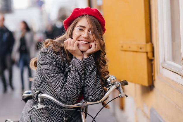 Felice ragazza timida con capelli castani in posa sulla sfocatura dello sfondo della città in un giorno di autunno