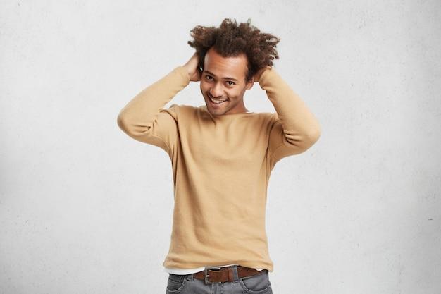 Довольный застенчивый мужчина с модной прической в свитере и джинсах чувствует себя неловко
