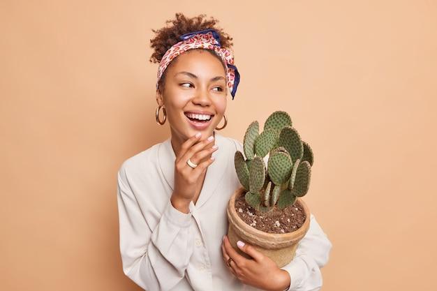 Felice e sincera donna afroamericana porta un vaso di piante d'appartamento a cui piacciono i cactus