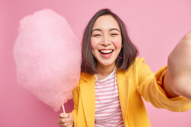 Радостная искренняя азиатская женщина выражает настоящие эмоции, держит вкусную сахарную вату, улыбается позитивно, имеет хорошее настроение во время летней прогулки, носит стильную одежду, изолированную на розовой стене.