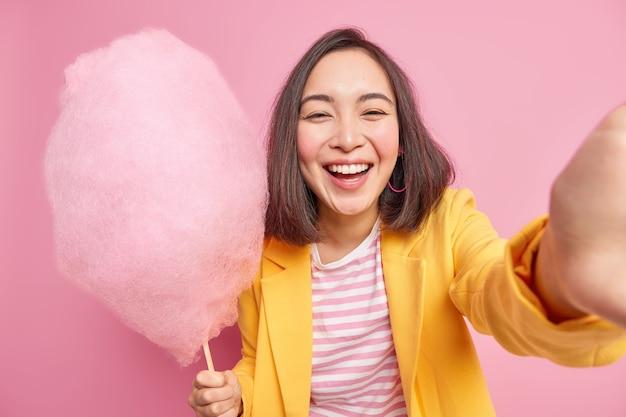 Felice sincera donna asiatica esprime emozioni autentiche tiene gustoso zucchero filato fa sorrisi selfie positivamente ha buon umore durante la passeggiata estiva indossa abiti eleganti isolati sul muro rosa