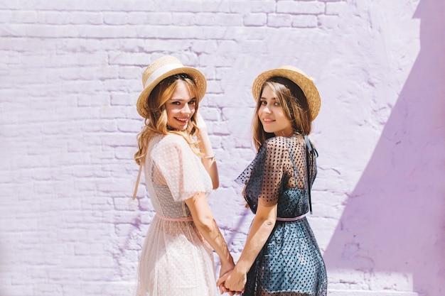 Радостные сестры в подобных платьях с вдохновенной улыбкой оглядываются через плечо в солнечный день