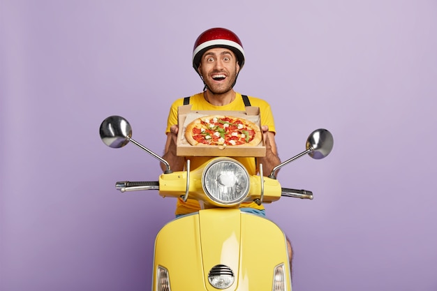 Glad skilled deliveryman driving yellow scooter while holding pizza box