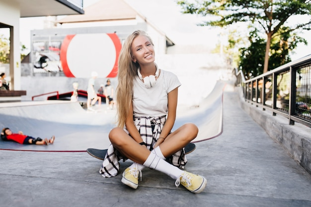 Glad slim woman sitting on longboard after training. outdoor portrait of pretty blonde female model posing in skate park in weekend.