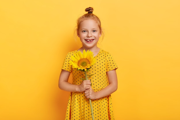 Glad small red haired girl posing with sunflower in yellow dress