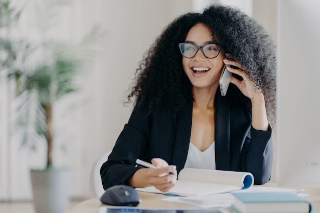Glad smiling dark skinned woman calls business partner, being in good mood, makes notes, sits at workplace
