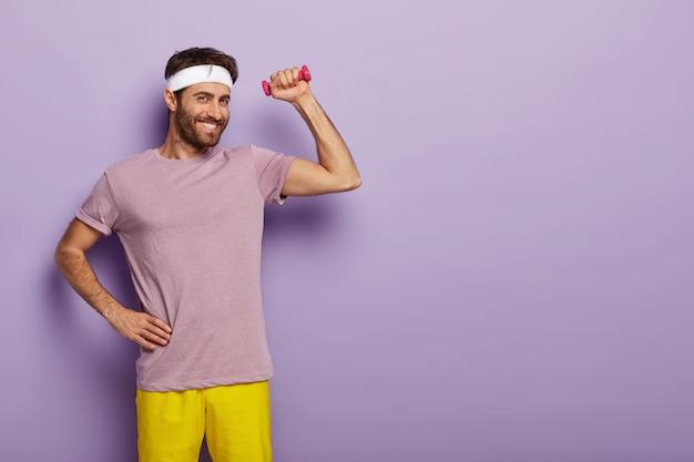 기쁜 웃는 남자 체조 선수는 허리에 한 손을 유지