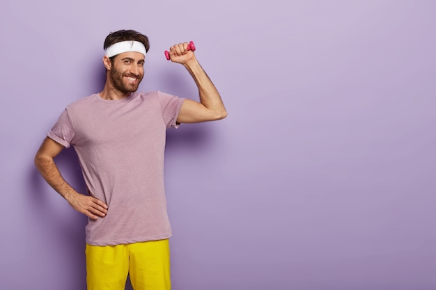 La ginnasta maschio sorridente felice tiene una mano sulla vita