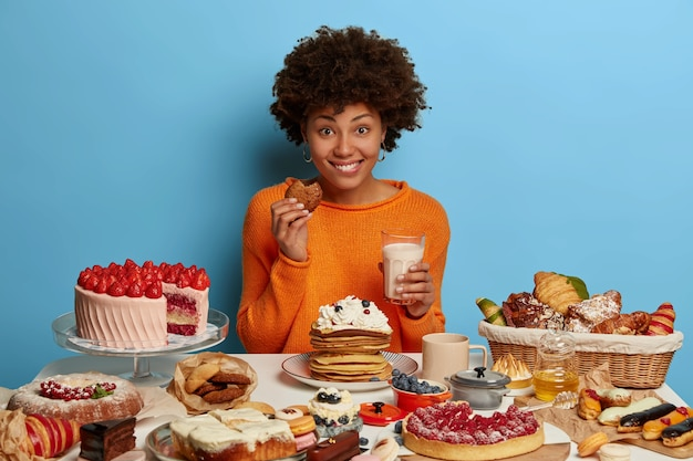 Glad smiling woman with afro curly hairdo eats tasty pastry with milk, has good mood to eat delicious desserts, tries yummy just baked cookies