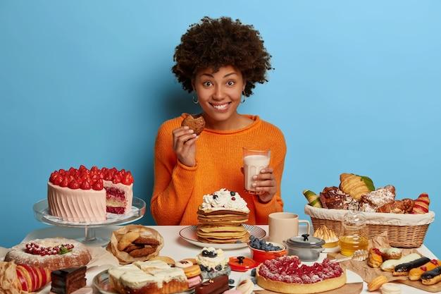 アフロ巻き毛の嬉しい笑顔の女性は、ミルクと一緒においしいペストリーを食べ、おいしいデザートを食べる気分が良く、焼きたてのおいしいクッキーを試してみます