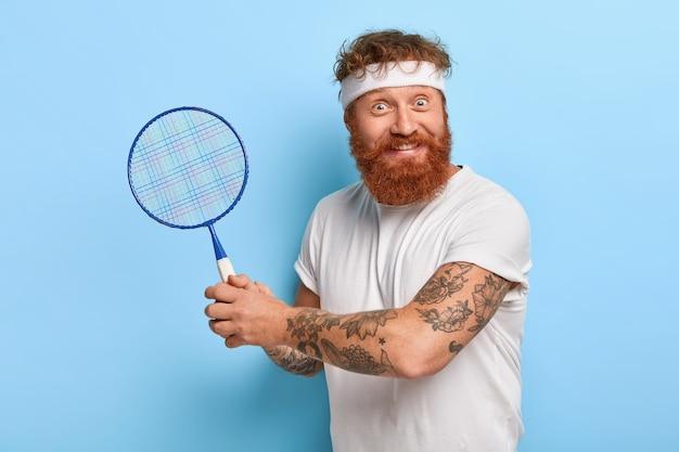 Il giocatore di sport contento tiene la racchetta da tennis, indossa la fascia bianca, maglietta