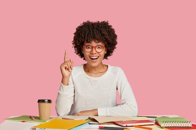 Ragazza studentessa felice in posa alla scrivania contro il muro rosa