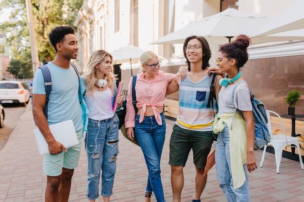 新しい冗談を言っている眼鏡をかけたアジアの友人に耳を傾けるうれしい学生。女の子はジーンズと流行のヘッドホンを身に着けて、カフェの横の路上で仲間と時間を過ごします。