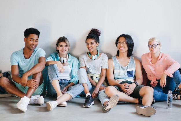 Довольные студенты в стильных кроссовках и аксессуарах сидят на полу со скрещенными ногами. возбужденные молодые люди разных национальностей отдыхают в светлой комнате и смеются.