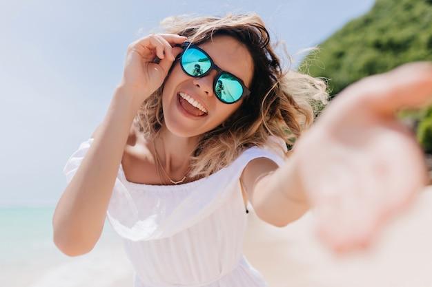 열 대 섬에서 재미 스파클 안경에 다행 세련 된 여자. 여름 휴식 시간 동안 긍정적 인 감정을 표현하는 물결 모양의 머리를 가진 멋진 여자의 야외 사진.