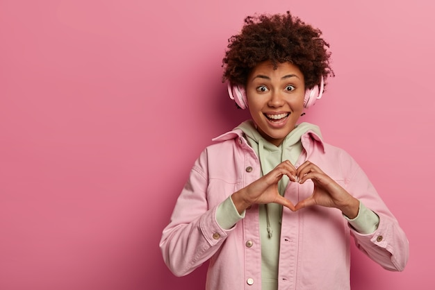 Glad teenage woman makes heart gesture over chest, expresses affection