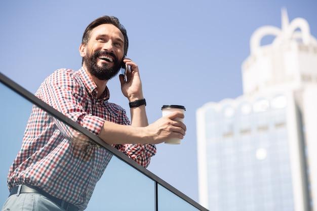 Рад поговорить с вами. веселый бородатый мужчина пьет кофе и разговаривает в городе