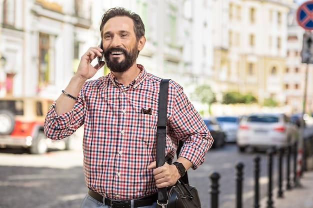 よろしくお願いします。通りを歩きながら電話で話している陽気な喜んでいる男の腰を上げる