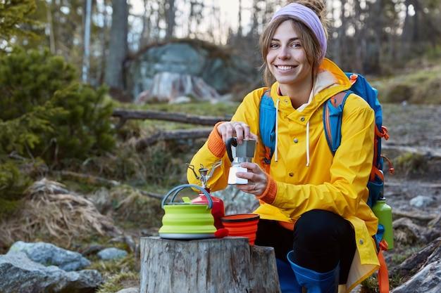 Felice turista tiene la caffettiera, fa un picnic sul ceppo, indossa una sciarpa sulla testa, impermeabile giallo