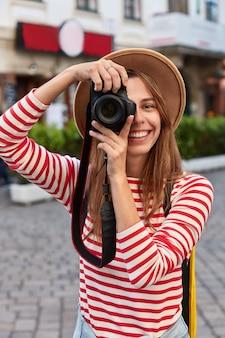 Il turista felice fa foto professionali con la fotocamera, sorride ampiamente, si concentra su un bellissimo punto di riferimento, passeggia nel centro della città, indossa un cappello