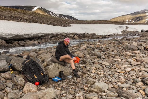 A glad tourist wipes himself after he crossed cold creek,autumn, sarek
