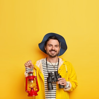 Glad unshaven man carries binoculars and oil lamp, wears hat and raincoat, has mustache, smiles pleasantly, stands against yellow wall