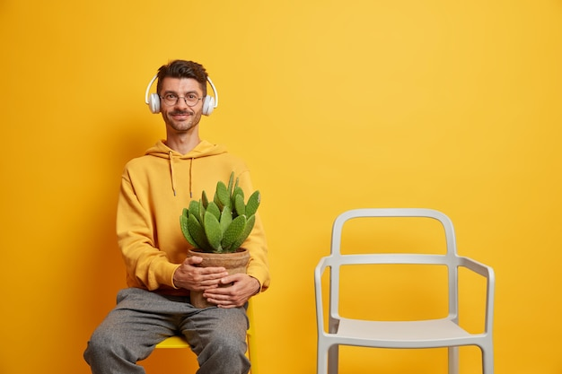 Glad unshaven man listens music in stereo headphones holds potted cactus dressed in casual wear poses on chair