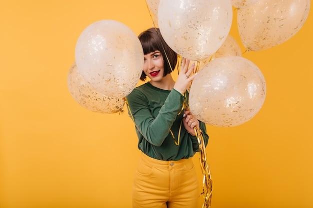 파티 풍선 뒤에 숨어 다행 백인 여성 모델. 생일을 축하하는 녹색 스웨터에 평온한 갈색 머리 소녀의 실내 사진.