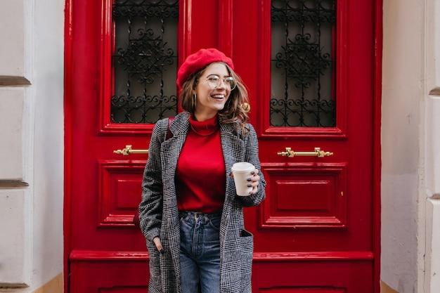 긴 회색 재킷에 기쁜 백인 여성 모델은 빨간 문 근처에 서있는 미소로 멀리보고