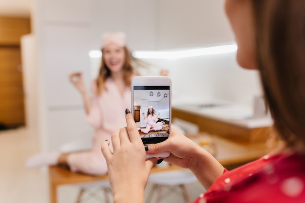 Glad white girl eating pizza and playing with her hair. brunette woman holding smartphone and taking picture of friend in kitchen with light interior.