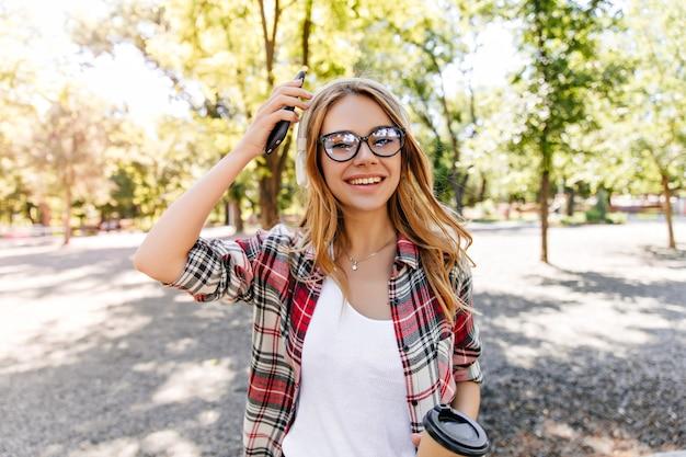 공원에서 시간을 보내는 스파클 안경에 다행 백인 소녀. 봄 주말을 즐기는 금발 머리를 가진 사랑스러운 여성 모델.