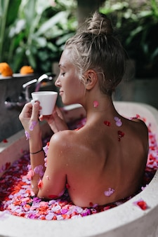 Glad white woman sitting in bath with rose petals and drinking tea with eyes closed. portrait from back of inspired caucasian female model enjoying coffee during morning spa.