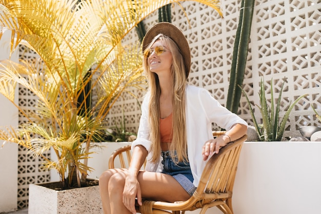 週末にリゾートレストランで休んでいるデニムのショートパンツでうれしい白人の若い女性。屋外カフェでポーズをとって金髪の魅力的な女性の笑顔。