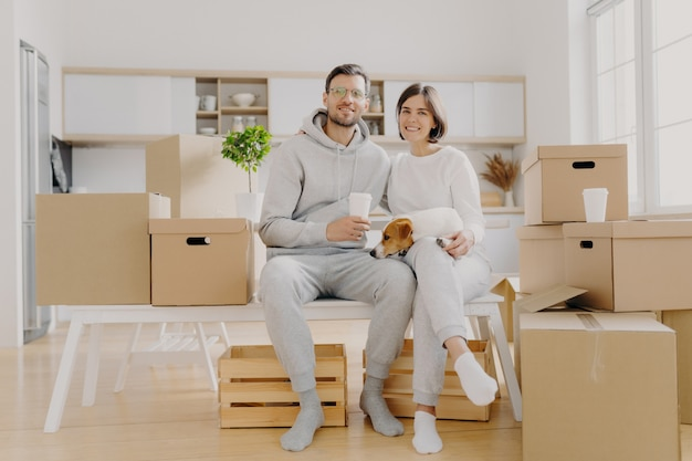Glad wife and husband sit closely to each other, have good mood, being happy owners of new flat, drink takeout coffee, pose with pedigree dog, surrounded with packages. new beginning