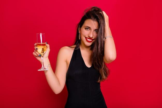 춤과 샴페인을 들고 다행 여자. 즐거운 얼굴 표정으로 파티에서 재미 긴 갈색 머리를 가진 예쁜 아가씨의 실내 사진.