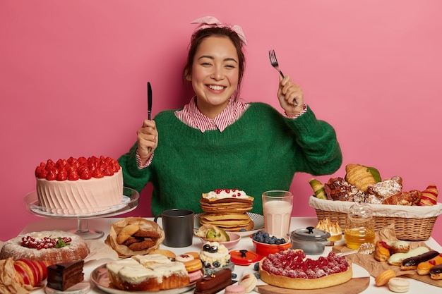 嬉しい女性はフォークとナイフを持っており、甘いデザートを食べる食欲があり、歯を見せる笑顔があり、ピンクの壁に隔離されたおいしい料理を楽しんでいます。