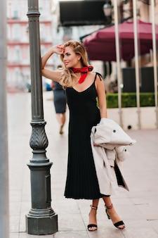 Счастливая женщина в черном платье со складками ждет кого-то на улице, прислонившись к железной колонне