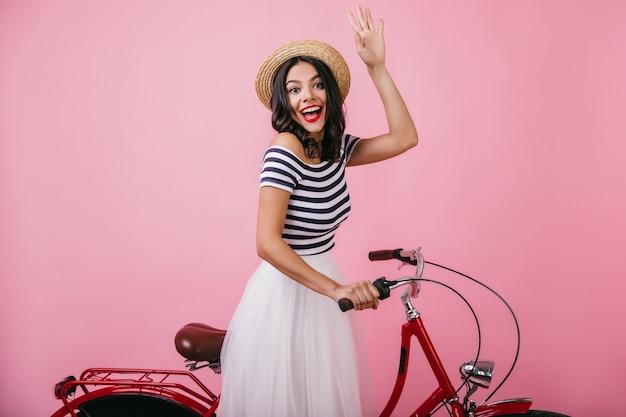 驚きの笑顔で自転車にポーズをとる麦わら帽子の嬉しい女性。幸せな感情を表現する魅力的なブルネットの女の子の屋内ショット。