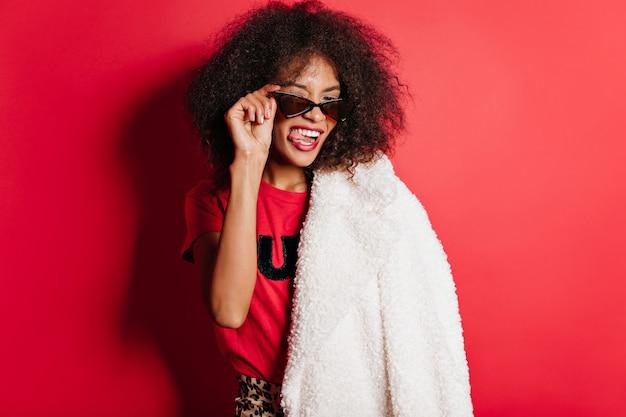 Счастливая женщина в солнцезащитных очках корчит лица на красной стене