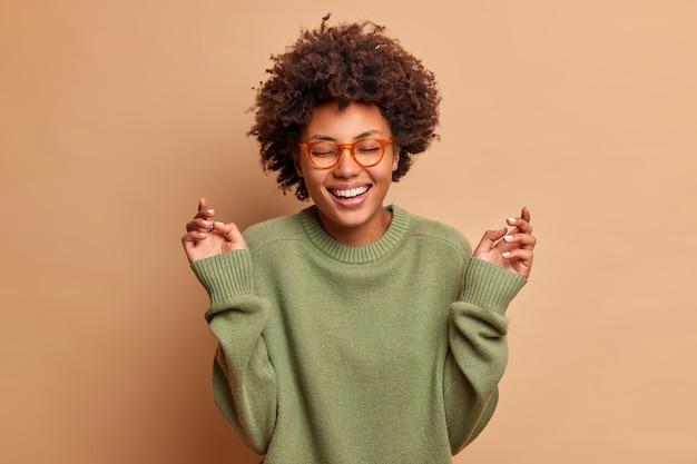 Довольная женщина поднимает руки, имеет беззаботное жизнерадостное выражение, закрывает глаза, улыбается, зубасто носит оптические очки и свитер, изолированные на бежевой стене
