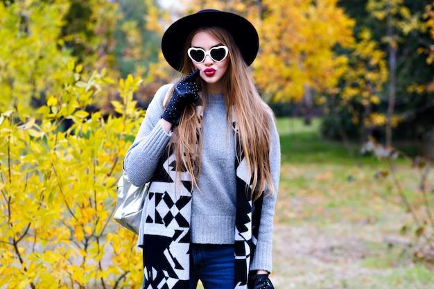 嬉しい女性は晴れた秋の日にエレガントなコートとサングラスでポーズをとる黒い帽子を着ています。黄色の木のある公園を歩いてトレンディな灰色のセーターで熱狂的な女性モデルの屋外のポートレート。