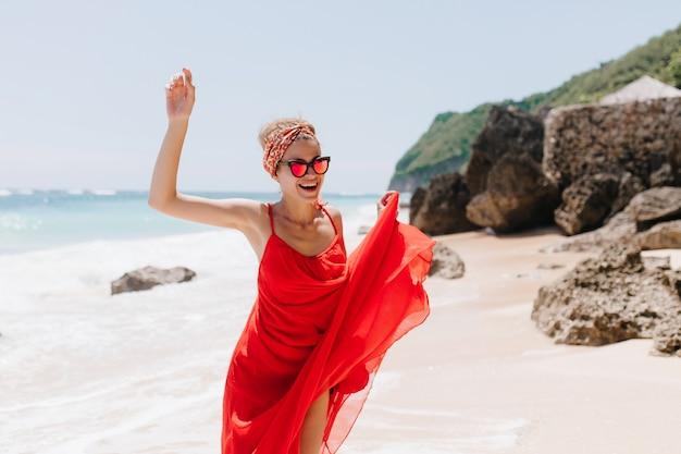 Счастливая женщина носит ленту и солнцезащитные очки, танцуя на диком пляже. фотография довольной загорелой девушки, выражающей положительные эмоции на пляже на открытом воздухе