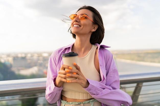 スタイリッシュな夏の衣装で短い髪の嬉しい女性は、モダンな橋でコーヒーを飲みます