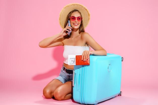 Довольная женщина с чемоданом, билетами наличными и паспортом собирается путешествовать, бронируя отель по телефону