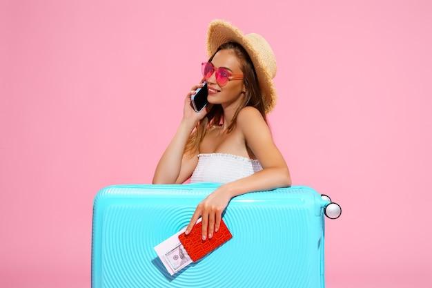 Довольная женщина с чемоданом, билетами, деньгами и паспортом собирается путешествовать, бронируя отель по телефону