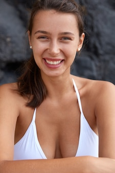 Glad woman with toothy smile, perfect breast, looks gladfully , dressed in swimsuit
